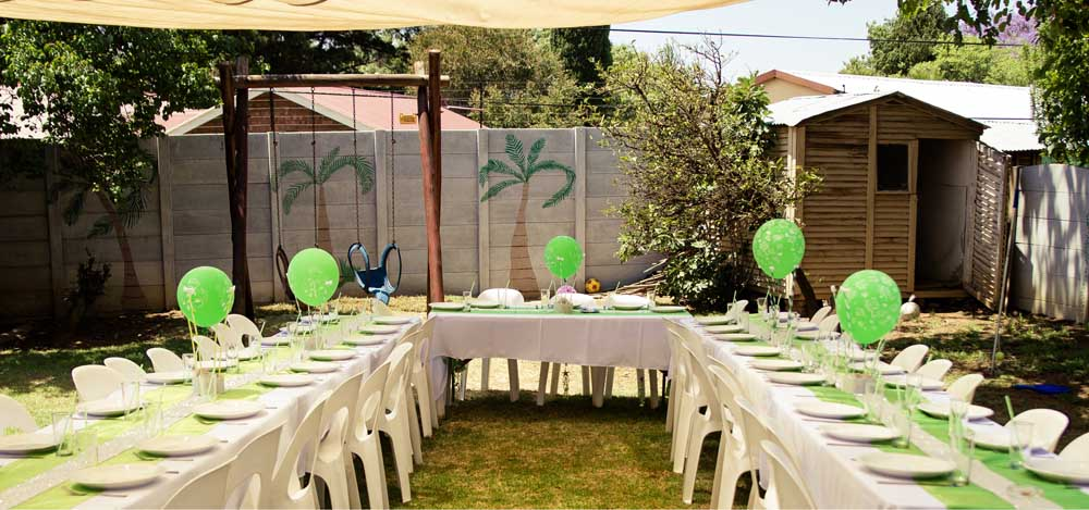 long tables, place settings, chairs, and balloons set up in a backyard