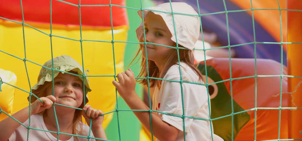 two little girls in a bounce castle smiling for the camera