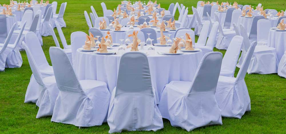 round tables, place settings and chairs set up outside for a wedding